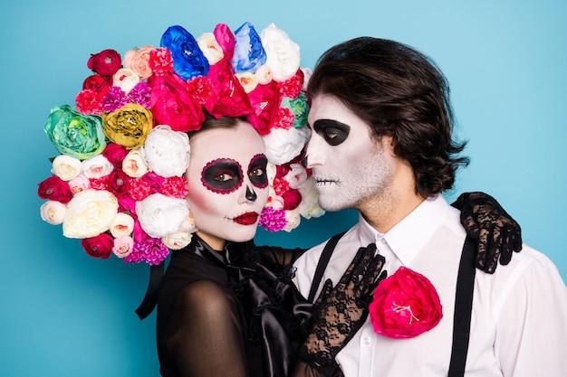 Любовь растапливает мертвые сердца. фотография жутко пугающей пары мужчина леди обнимаются темные монстры в черном платье костюм смерти розы повязка на подтяжках изолированный синий цвет фона