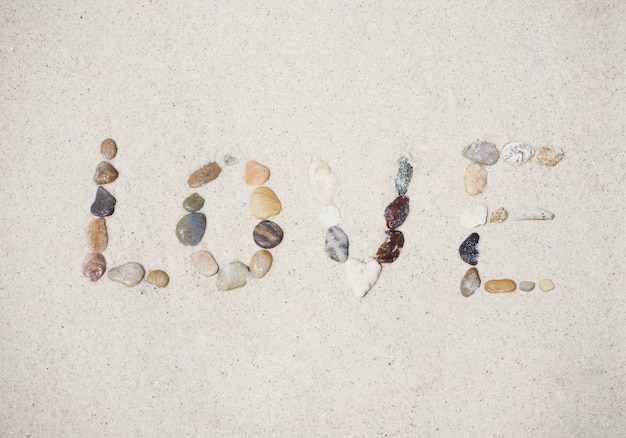 Love message made of pebble on sand summer beach