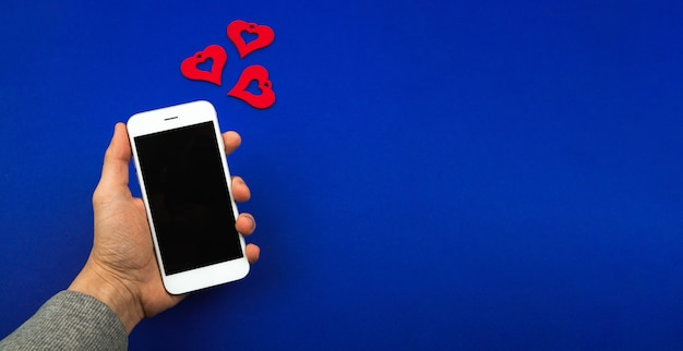 휴일에 사랑의 메시지, valintine의 날 카드, 하트 형태로 알림이 있는 스마트폰을 들고 있는 남자와 흉내냅니다. 고품질 사진