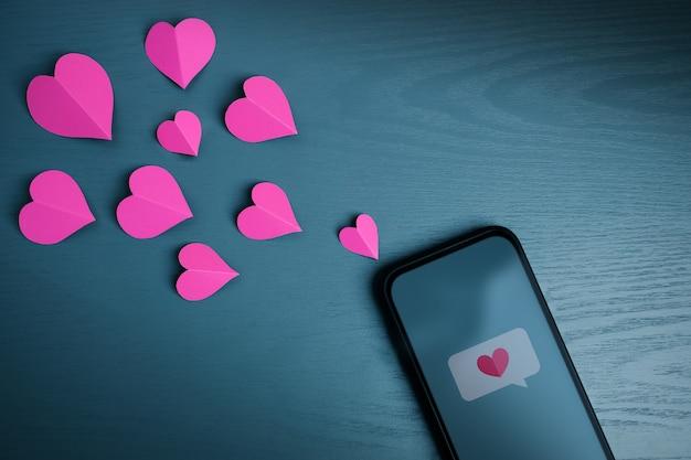 사랑의 메시지. 발렌타인 데이 개념. 휴대폰을 통해 누군가에게 하트 심볼을 전송합니다. 평면도