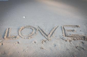 砂の背景に書かれた愛のメッセージ