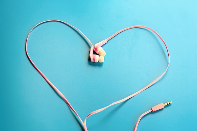 Love music concept pink headphones in the form of a heart on a blue background