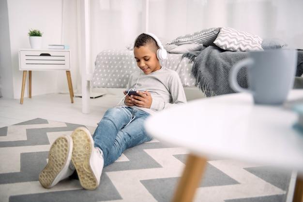 Любить музыку. оптимистичный афро-американский мальчик в наушниках, глядя на экран телефона