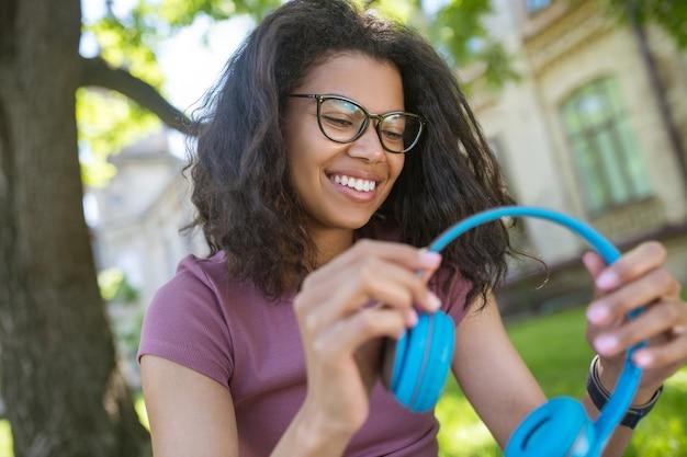 Любить музыку. улыбающаяся мечтательная молодая девушка в наушниках, слушающая музыку