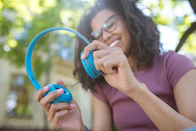 Любить музыку. улыбающаяся мечтательная молодая девушка в наушниках, слушающая музыку Premium Фотографии