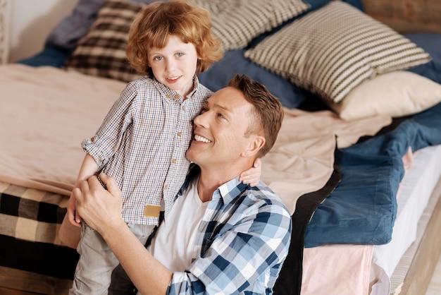 아빠를 사랑해. 곱슬 머리가 카메라를 똑바로보고 아버지의 목에 왼손을 유지하는 매력적인 소년