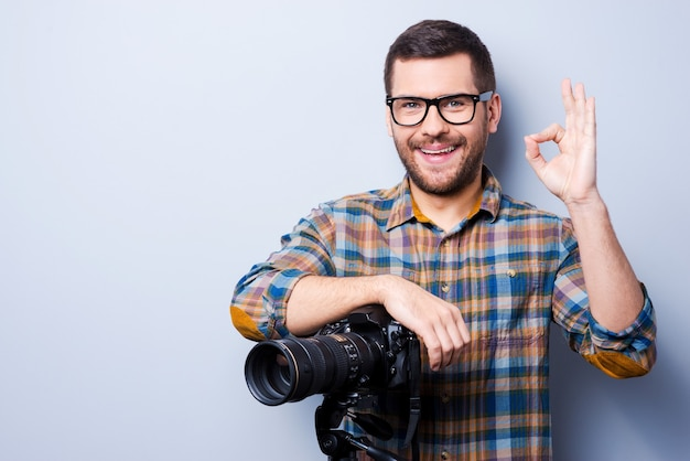Love my job. portrait of confident young man in shirt holding hand on camera on tripod and gesturing while standing against grey background