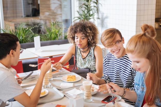 私の学校が大好きです。友達の近くに座ってデザートを食べる集中国際女性