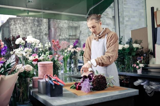 私の仕事が大好きです。職場に立って花束を作るハンサムな男性