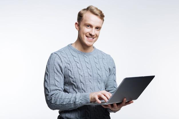 私の仕事が大好きです。ラップトップで作業し、灰色の背景に孤立して立っている間笑顔の灰色のセーターのハンサムな若い男