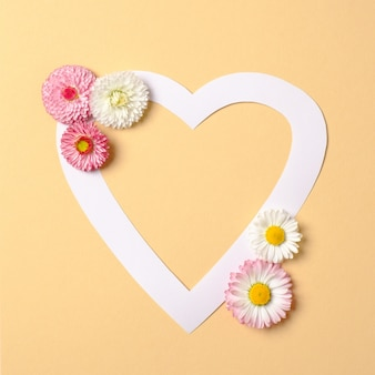 Love nature concept. daisy flowers and white heart-shaped paper card on pastel yellow background.