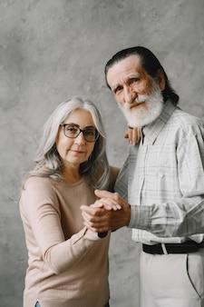 愛は決して古くなりません。リビングルームで踊るうれしそうなアクティブな古い引退したロマンチックなカップル。