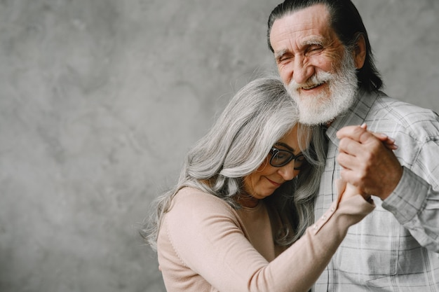 Love never grows old. joyful active old retired romantic couple dancing in living room.