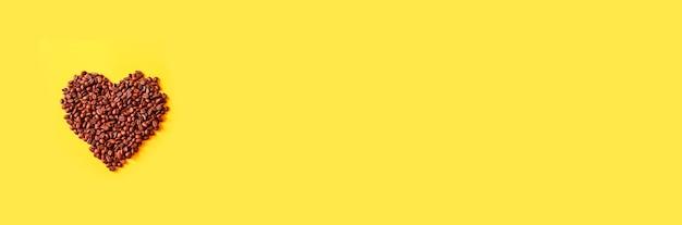 커피의 사랑, 노란색 바탕에 커피 콩의 심장. 최소한의 구성. 평면 위치, 평면도, 복사 공간
