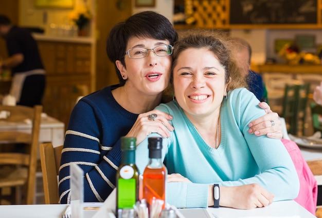 Любовь матери и дочери. счастливые женщины в хорошем кафе с копией пространства на размытом фоне. пожилая женщина и ее взрослая дочь в кафе. день матери.