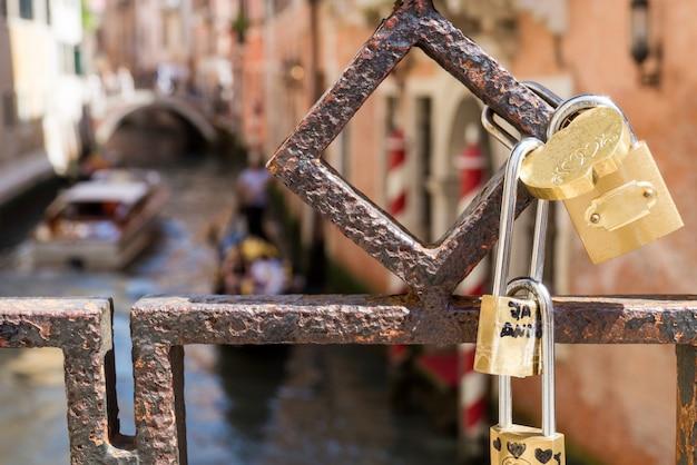 Love padlocks attached to bridge in venice