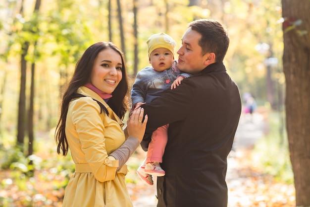 Любовь, отцовство, семья, сезон и люди концепции - улыбающаяся пара с ребенком в осеннем парке