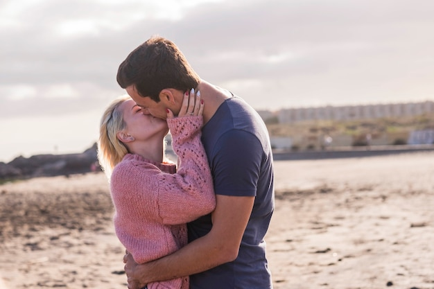 Love and passion for caucasian young couple in outdoor leisure activity. romantic and tenderness kiss with man and girl at the beach under the sun light. summer love concept
