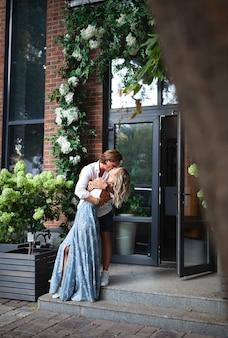 屋外で情熱的なカップルが大好きです。街の通りで官能的なキス。ロマンチックなラブストーリー、ファッショナブルなスタイリッシュな女性を抱き締めるハンサムな男。ナチュラルカラーのライフスタイル、フルハイト