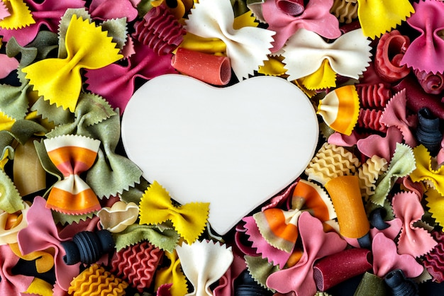 Love pasta. multicolored pasta and heart, top view. background.