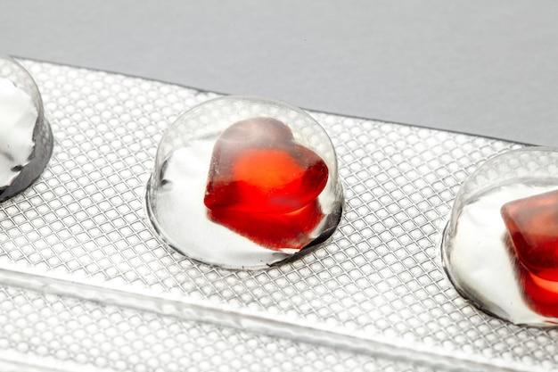 愛の丸薬赤いハート型の丸薬が入ったブリスターパック愛好家や効力のための錠剤灰色の背景