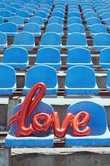 Love red foil balloon on blue stadium seats