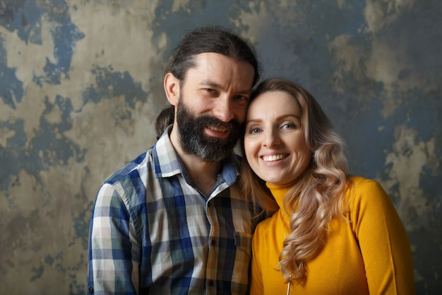 Love and relationship concept. happy adult couple hugging, smiling wide and looking at camera, standing together on blue abstract background