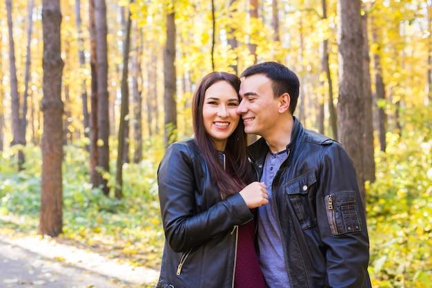 Концепция любви, отношений, семьи и людей - улыбающаяся пара, обнимающая в осеннем парке.
