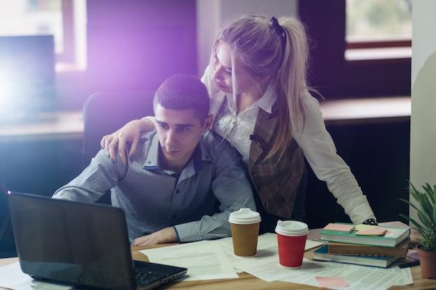 사랑의 관계. 사무실 일. 직장 로맨스. 동료의 친밀감. 책상에서 일하는 남자를 포옹하는 여자.