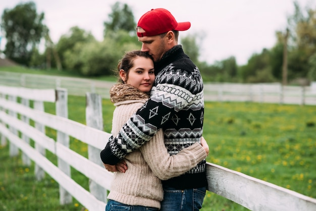 Love and relationship between a woman and a man. concept of a young family. couple in love hugs. a man kisses his woman. happy couple at outdoors. young couple in the village