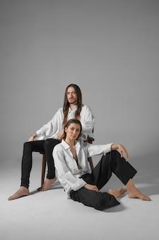 愛、関係、ファッション、スタイルのコンセプト。裸足でポーズをとる同様の服を着たファッショナブルなカップルの孤立した垂直方向の画像。床に座っている彼の妻と一緒に椅子でリラックスする支配的な男