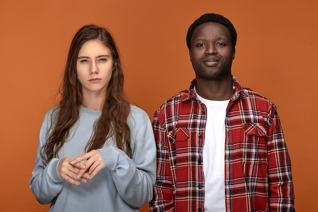 Love, relationships, people and lifestyle concept. fashionable interracial couple posing isolated having annoyed irritated looks, expressing negative attitude, grimacing, woman being suspicious