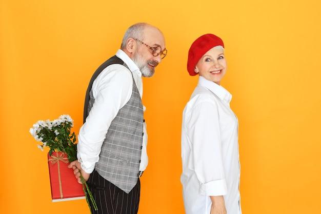 愛、ロマンス、愛情の概念。背中の後ろに贈り物と花粉を保持し、赤いベレー帽の美しい成熟した女性に驚きを与えるひげとハゲのエレガントな年配の男性の孤立した画像