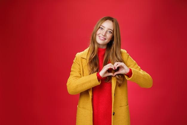 愛、ロマンス、秋のコンセプト。黄色のコートを着た魅力的な優しくて優しい若い赤毛の女性の肖像画は、赤い壁の上のカメラでかわいい笑顔で、同情で告白する心のジェスチャーを示しています。