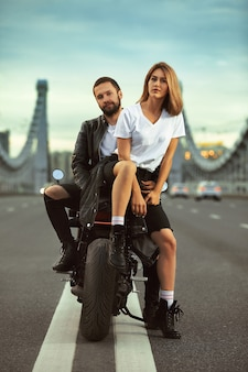 Love and romantic concept beautiful couple on motorcycle in the middle of the road on the bridge, on double solid.