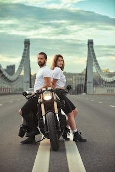 Love and romantic concept. beautiful couple on motorcycle stands opposite each other in the middle of the road on the bridge, on double solid.