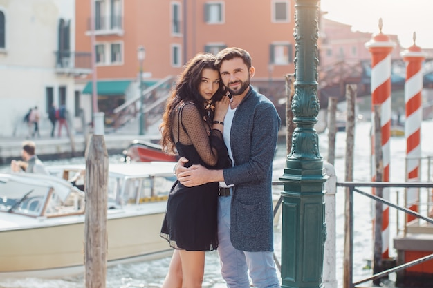Love - romantic couple in venice on pier. young couple on travel vacation holidays hugging