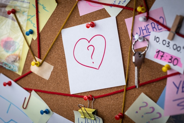 Love search . close-up view of a detective board with evidence. in the center is a white sheet attached with a red pin with the heart icon