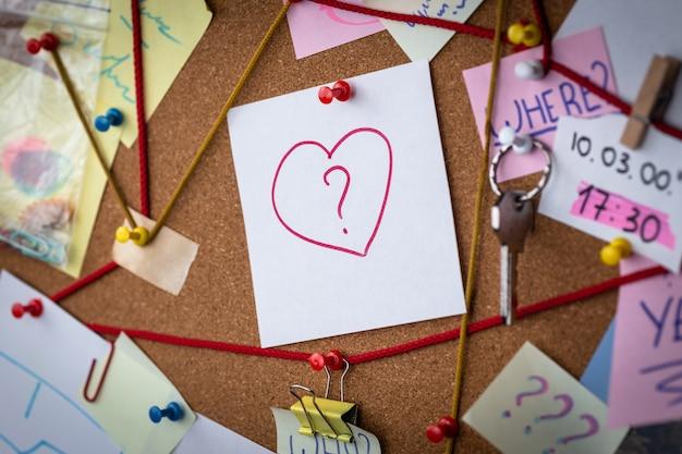 사랑 검색. 증거와 탐정 보드의 근접 촬영보기입니다. 가운데에는 심장 아이콘이있는 빨간 핀이 붙어있는 하얀 시트가 있습니다.