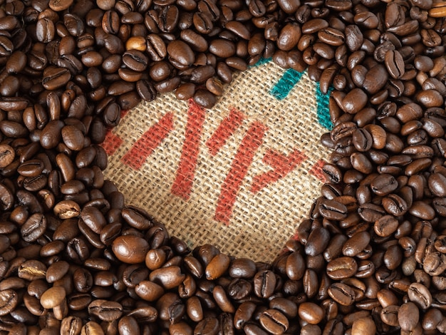 Love shape coffee beans on linen texture background
