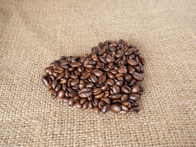 Кофейные зерна в форме любви на фоне текстуры льна