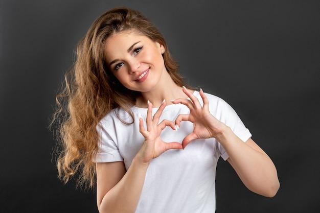 사랑 기호입니다. 낭만적인 메시지. 심장 제스처를 보여주는 쾌활 한 여자