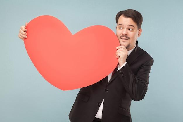 愛、聖。バレンタインのコンセプト。近くを見て大きな心を持っているビジネスマン。屋内、スタジオショット、水色または灰色の背景に分離