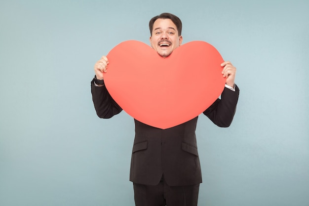 愛、聖。バレンタインのコンセプト。大きな赤いハートを持っている表現ビジネスマン。屋内、スタジオショット、水色または灰色の背景に分離