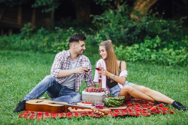 Love story.beautiful couple enjoying picnic time outdoor,they are sitting in blanket carpet