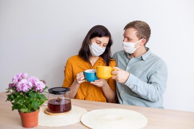 무균 마스크에 격리 된 사랑 이야기 가족 남편 아내 남자 친구 여자 친구. 정상적인 생활 코로나 바이러스로 차를 마신다. 라이프 스타일 covid-19. 검역 바이러스 보호 무균 가정 함께