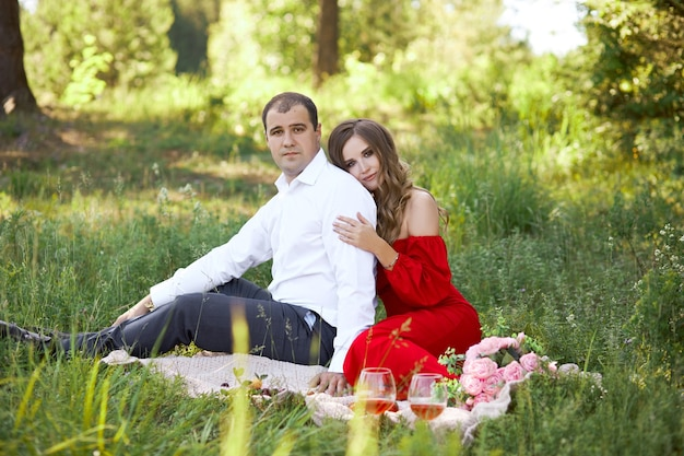 Love story of a loving couple of men and women in the spring in nature in the forest. couple hugs, picnic in the park