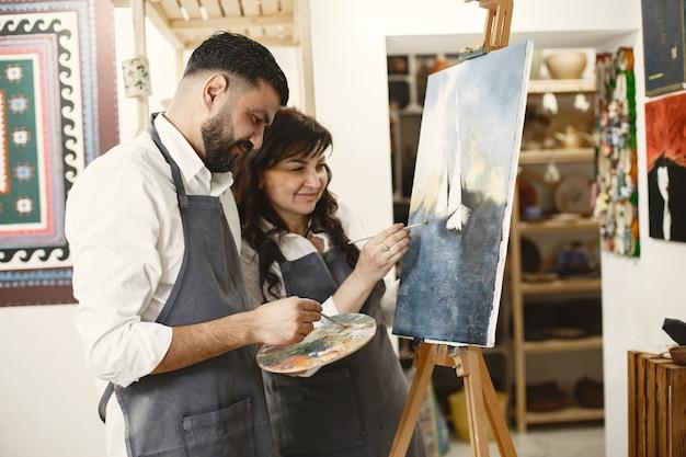 아트 스튜디오에서 성인 커플의 사랑 이야기. 그들은 그림을 그리고, 웃고, 서로 키스합니다. 그들의 감정, 감정, 사랑.