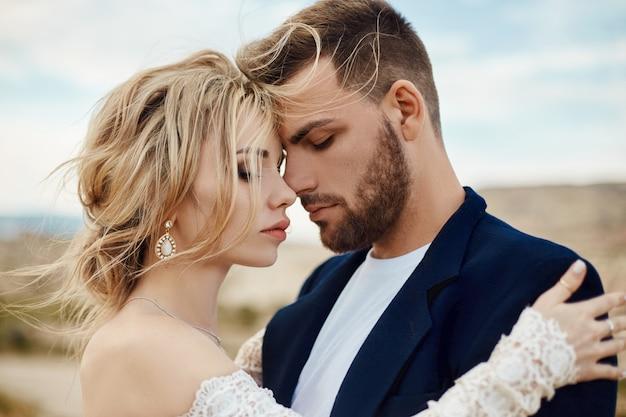 여자와 남자의 사랑 이야기. 사랑하는 부부, 아름다운 동양 부부를 포용합니다. 재킷과 긴 고급스러운 가벼운 드레스를 입은 여성