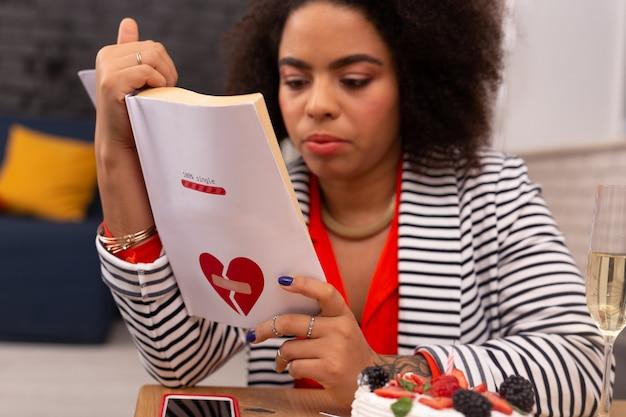 사랑 이야기. 좋은 아프리카 미국 여자의 손에있는 책의 선택적 초점